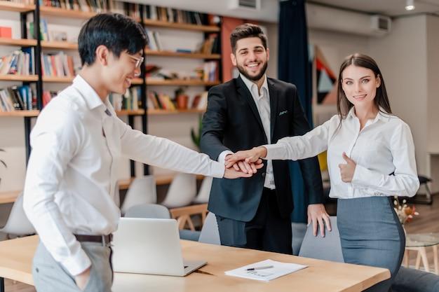 Felice squadra di collaboratori in ufficio, tenendosi per mano in gruppo
