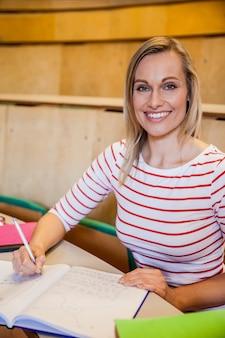 Felice studentessa scrivendo note all'università