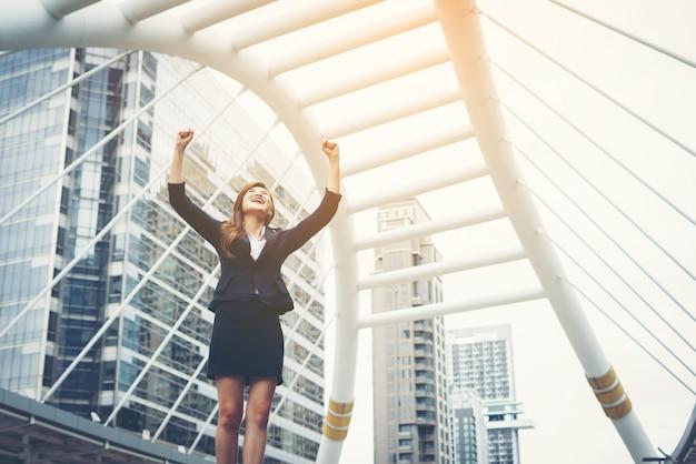 Felice successo businesswoman che si affaccia nel centro città mani sollevate.