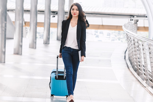 Felice successo imprenditrice camminando con i bagagli