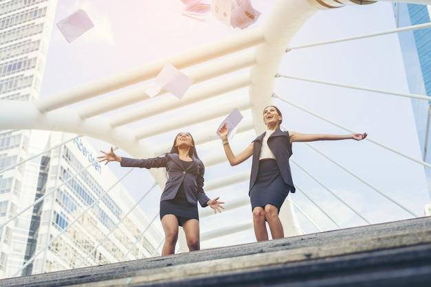 Felice successo le donne di affari che si affacciano sullo sbocco del centro città le mani sollevate.