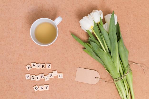 Felice testo della festa della mamma; tè al limone con fiori di tulipano bianco su sfondo marrone