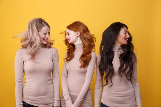 Felice tre donne che agitano i capelli.