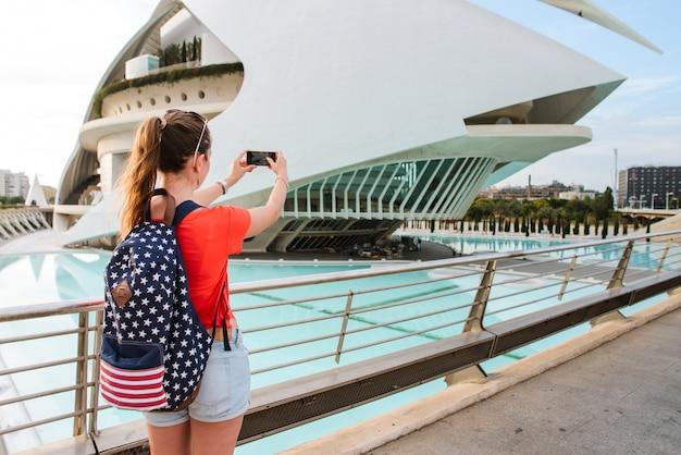 Felice turista femminile sta scattando una foto alla città delle arti e delle scienze a valencia