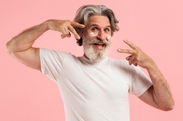 Felice uomo anziano con barba e crema