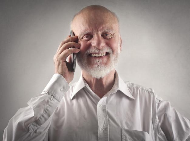 Felice uomo anziano sorridente parlando al telefono