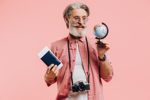 Felice uomo barbuto in occhiali da sole con una macchina fotografica e passaporto sceglie un paese sul globo per il viaggio.