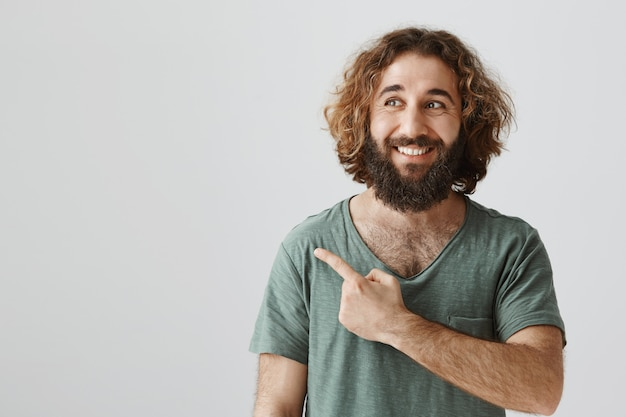 Felice uomo barbuto mediorientale bello che punta l'angolo superiore sinistro con espressione felice