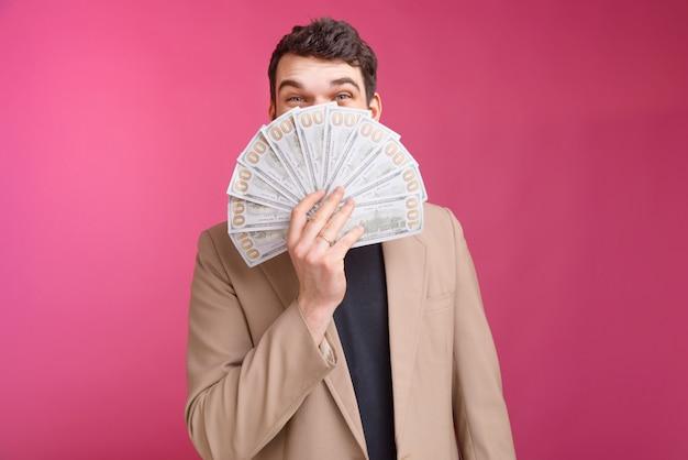 Felice uomo barbuto si copre il viso con un mucchio di dollari e denaro.