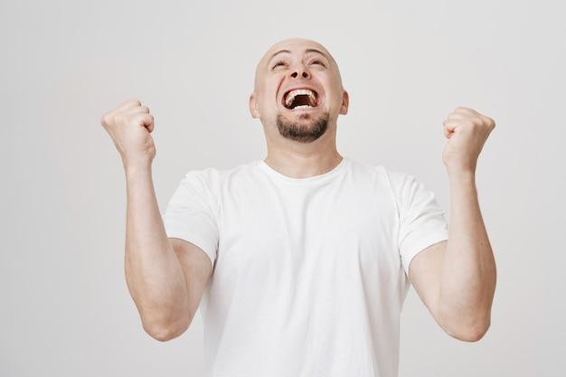 Felice uomo calvo pompa pugno, rallegrandosi per la vittoria, dì di sì