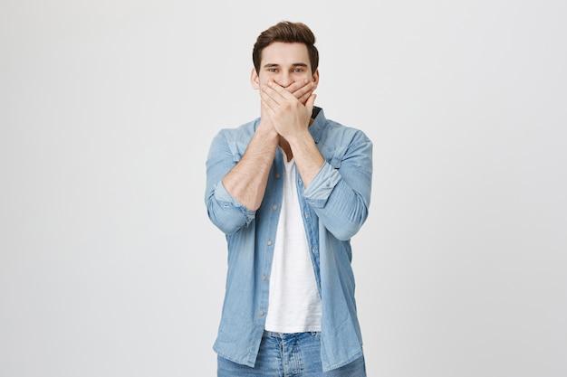 Felice uomo caucasico ridendo, coprire la bocca mentre ridacchia