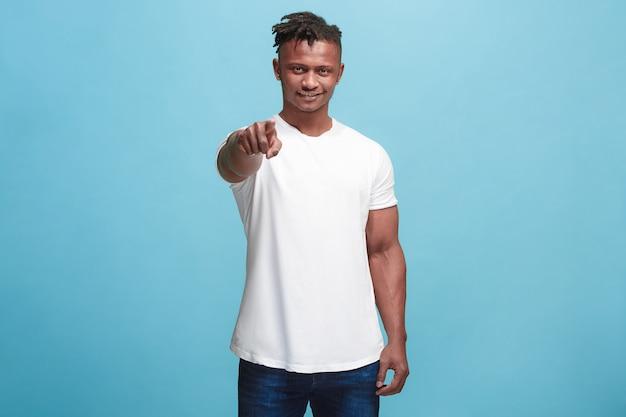 Felice uomo d'affari afro-americano indicarti e ti vogliono, ritratto di mezza lunghezza closeup sul blu