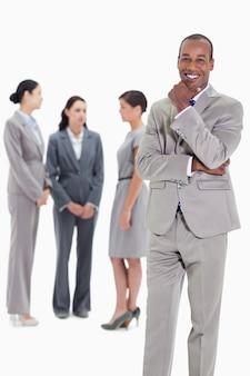 Felice uomo d'affari con i colleghi di lavoro in background