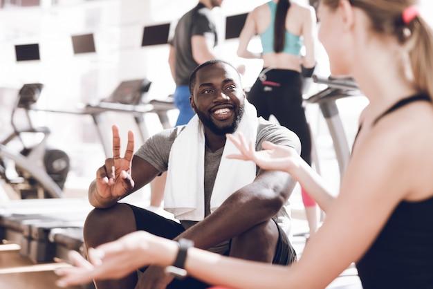 Felice uomo di colore si siede in palestra con un asciugamano intorno al collo