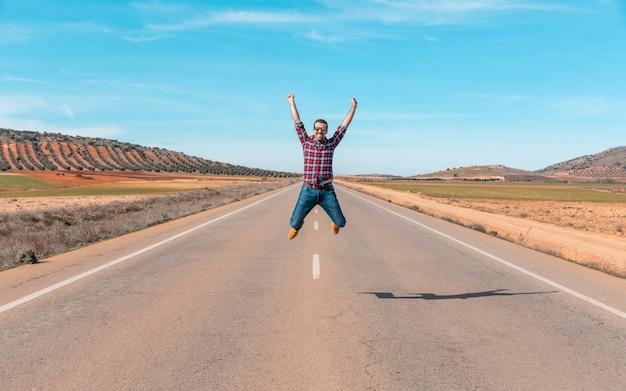 Felice uomo di successo che salta in una strada di campagna - il giovane che indossa la camicia a quadri trionfa in una vittoria con un salto e un braccio sollevato - concetti di felicità e successo, presi in spagna