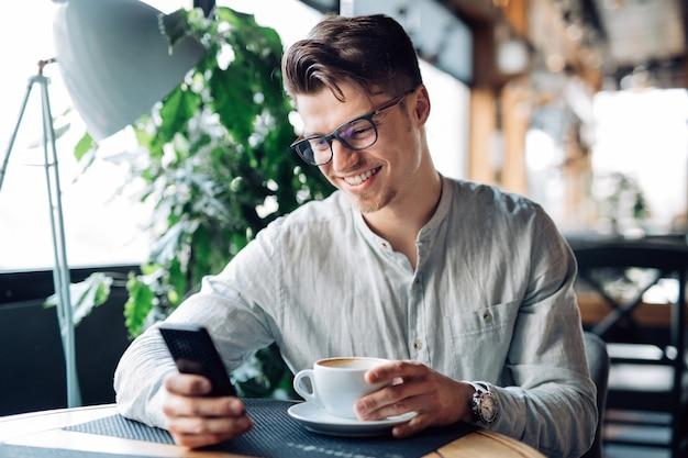 Felice uomo di successo in occhiali, utilizzando il cellulare, allegramente sorridente