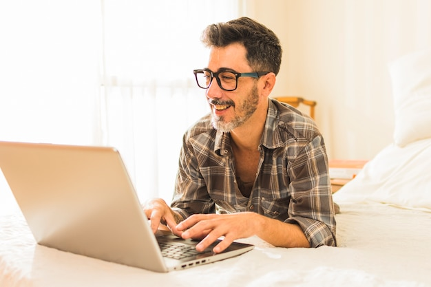 Felice uomo disteso sul letto accogliente utilizzando il computer portatile