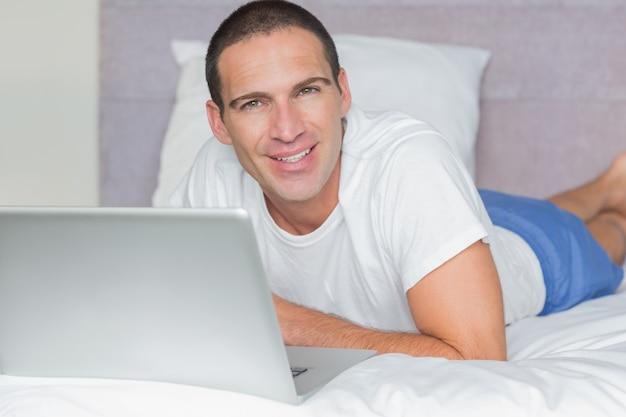 Felice uomo disteso sul letto usando il suo computer portatile