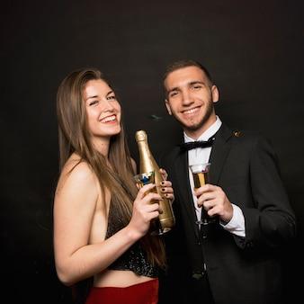 Felice uomo e donna con bottiglia e bicchieri di bevande