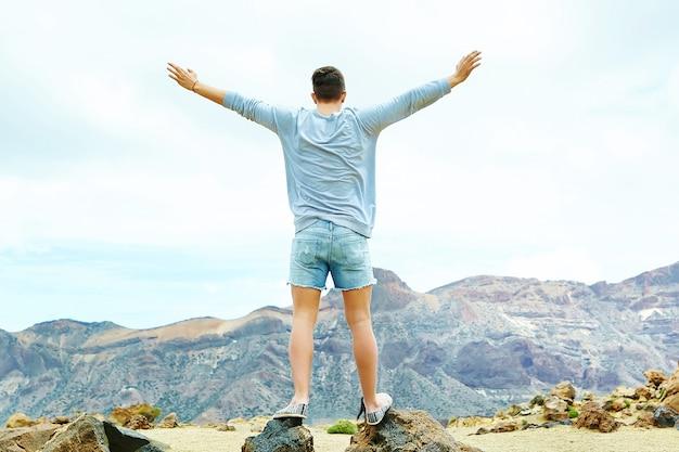 Felice uomo elegante in abiti casual casual in piedi sulla scogliera della montagna con le mani sollevate verso il sole e celebrando il successo