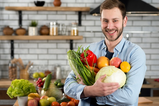 Felice uomo in piedi in cucina con verdure crude