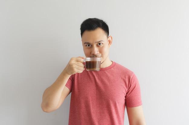 Felice uomo sano in maglietta rossa beve caffè o bevanda di erbe asiatiche.