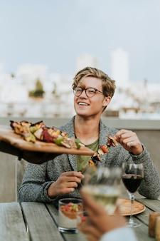 Felice uomo viene servito con spiedini barbecue vegano