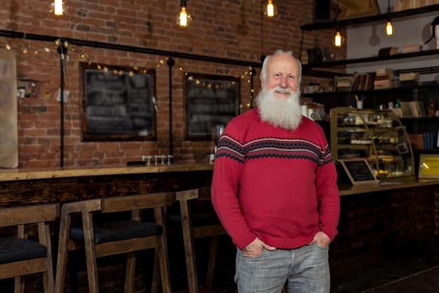 Felice vecchio con la barba nel caffè