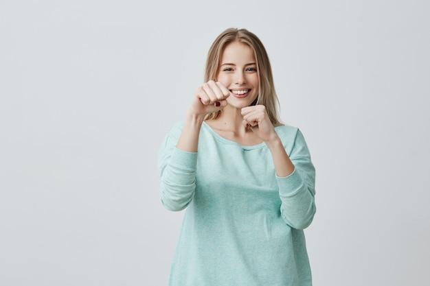 Felice vincitore di successo giovane donna bionda vestita casualmente mantenendo i pugni chiusi mentre tifo e sentirsi fortunati