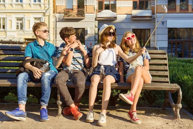 Felici 4 amici adolescenti o studenti delle scuole superiori si divertono, parlano
