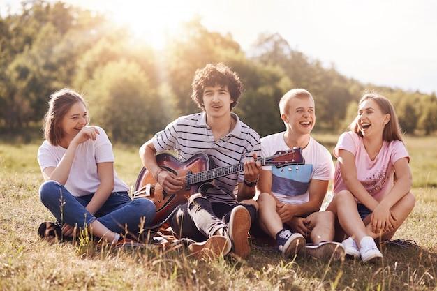 Felici amici femminili e maschili si godono il picnic all'aperto, siedono insieme, ridono e scherzano tra loro, cantano canzoni per chitarra