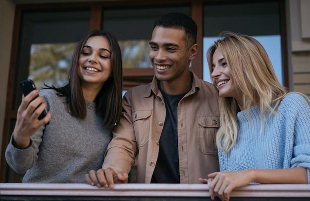 Felici amici multirazziali hipster che utilizzano smartphone, comunicazione insieme, visione di video