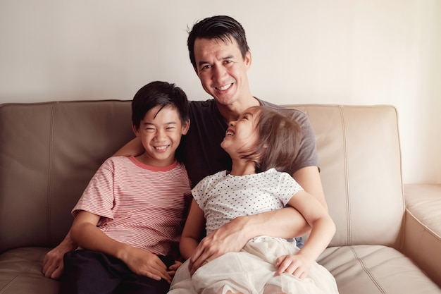 Felici bambini asiatici multiculturali con il padre a casa