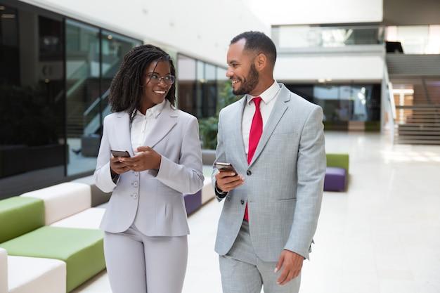 Felici colleghi di lavoro utilizzando telefoni cellulari e chat