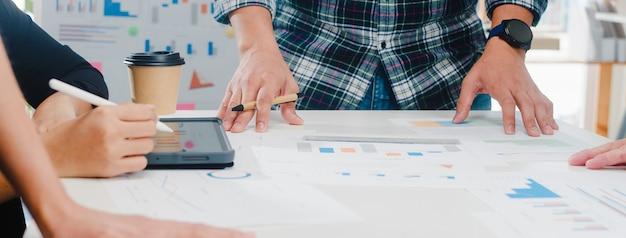 Felici giovani uomini d'affari asiatici e imprenditrici che incontrano idee di brainstorming su nuove scartoffie colleghi di progetto che lavorano insieme pianificando una strategia di successo godono del lavoro di squadra in un piccolo ufficio moderno.