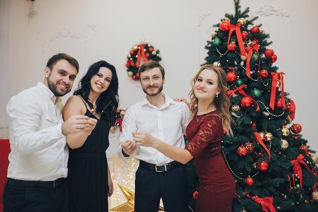 Felici ragazzi e ragazze che si godono la festa di capodanno con le luci del bengala