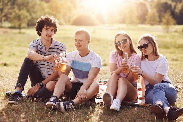 Felici ragazzi e ragazze festeggiano qualcosa, tintinnano bottiglie di birra durante il picnic, hanno espressioni positive, godono la giornata di sole estivo e la natura meravigliosa, sorridono con gioia. amicizia e concetto di riposo
