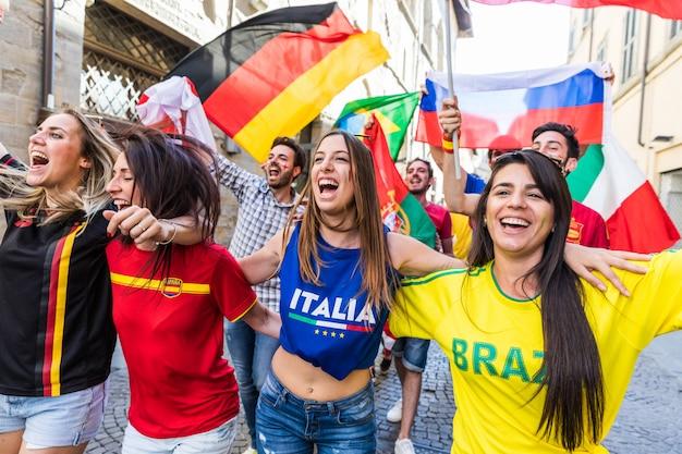 Felici sostenitori di fan di diversi paesi che camminano e cantano insieme