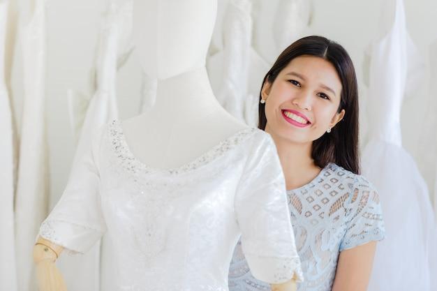 Felicità allegra delle donne asiatiche del ritratto nel deposito di modo di nozze