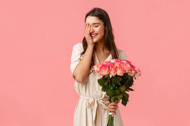 Felicità, amore e relazione concetto, sentirsi donna amata e apprezzata, attraente ragazza bruna in abito elegante, con rose, bouquet di fiori e sorridente, risata timida, rosa