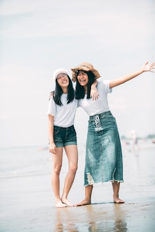 Felicità asiatica allegra dell'adolescente due sulla spiaggia del mare di vacanza