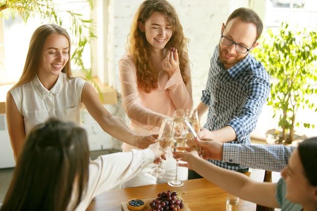Felicità. persone che tintinnano bicchieri di vino o champagne.