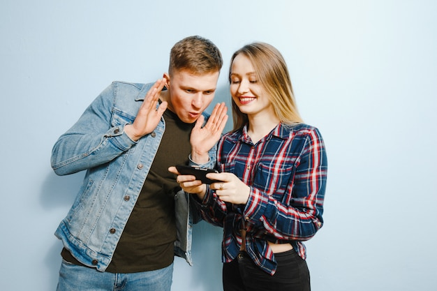 Felicità sul volto di due amici, su sfondo blu, guardando il telefono.