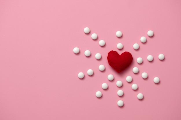 Feltro cuore rosso si trova su uno sfondo rosa