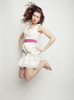 Femmina affascinante in vestito bianco che salta sopra la parete grigia