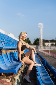 Femmina allegra alla seduta dello stadio