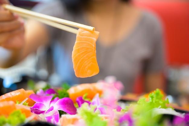 Femmina asiatica che mangia sashimi di color salmone
