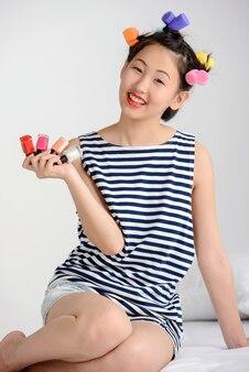 Femmina asiatica che si siede sul letto a casa e che fa pedicure