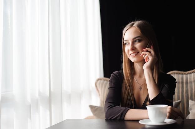 Femmina attraente con il sorriso sveglio che ha conversazione parlante