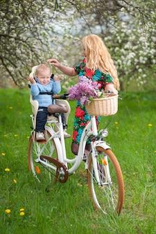 Femmina bionda con la bicicletta della città con il bambino nella sedia della bicicletta